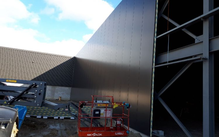 a picture of a construction site with a building being assembled with Structural Panels Isowall panels