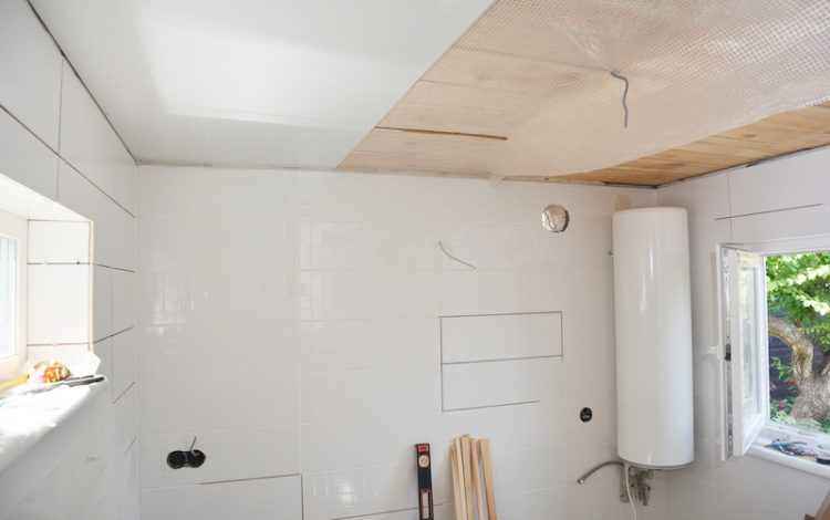 Installing white PVC Ceiling Boards in the new bathroom
